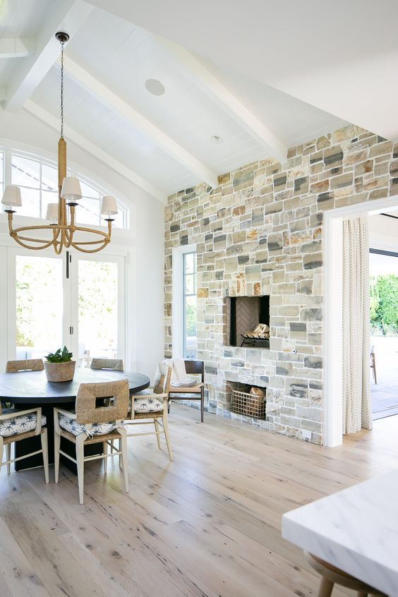a modern farmhouse dining space with a stone accent wall with a fireplace, a black round table and catchy chairs