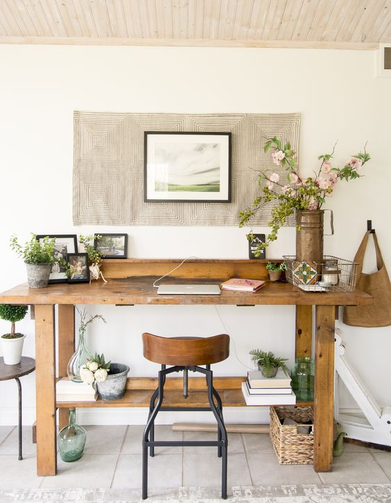 a modern farmhouse home office with a large wooden desk, an artwork on the wall, a wood and metal chair and baskets and plants