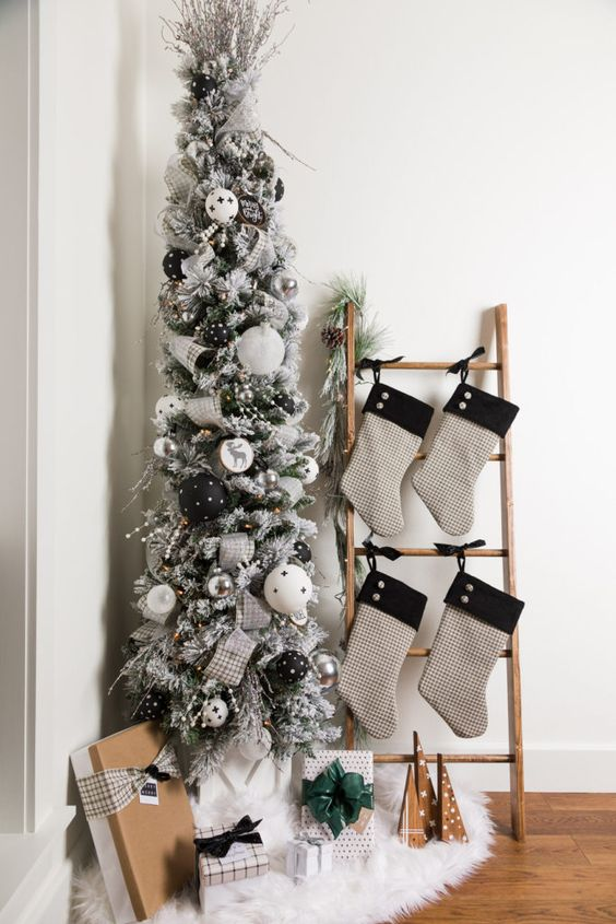 a modern flocked Christmas tree with white, black and silver ornaments, silver plaid ribbons and some berries is lovely