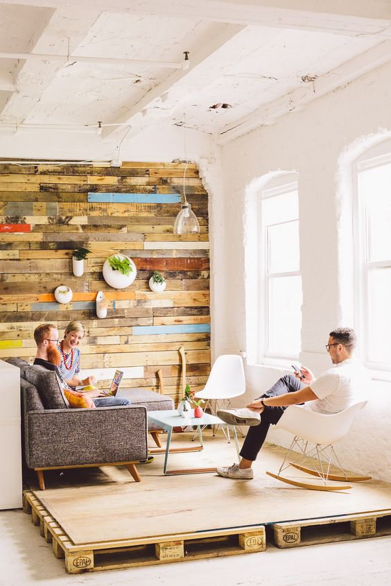 a modern living room with a conversation zone accented with a a colorful wooden wall, a platform, modern furniture and plants on the wall