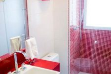 a modern red and white bathroom with a red tile shower space and a window, a red vanity and a square sink plus a red shelf