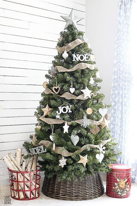 a modern rustic Christmas tree with burlap ribbons, wooden ornaments shaped as hearts, stars and snowflakes and a basket base