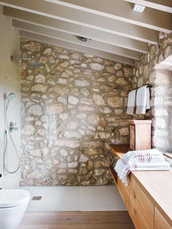 a modern rustic bathroom with a stone accent wall, a wooden floating vanity and an attic roof that make the space cozy