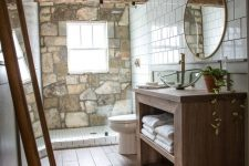 a modern rustic bathroom with a stone accent wall, wooden furniture, a round mirror and a glass bowl sink