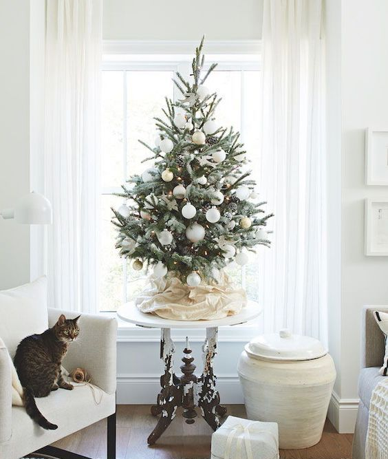 a modern snowy Christmas tree with lights, pinecones and white and gold ornaments looks beautiful and chic