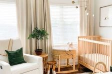 a neutral and cozy boho nursery with wooden furniture, a printed rug, a basket crib, neutral curtains and a potted plant