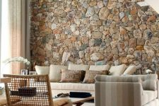 a stylish living room with a huge stone accent wall