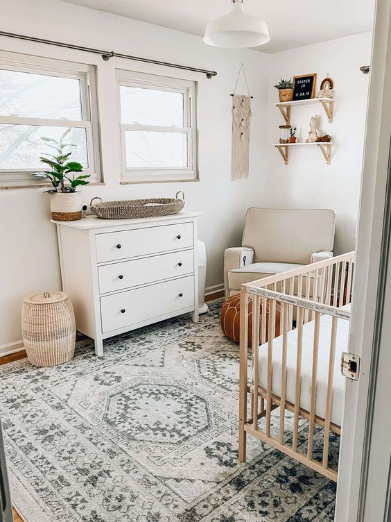 a neutral boho nursery with neutral and white furniture, printed textiles, a boho hanging on the wall, some potted plants and rugs