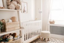 a neutral boho nursery with white furniture, a Moroccan rug, a shelving unit and white textiles is very cozy and chic