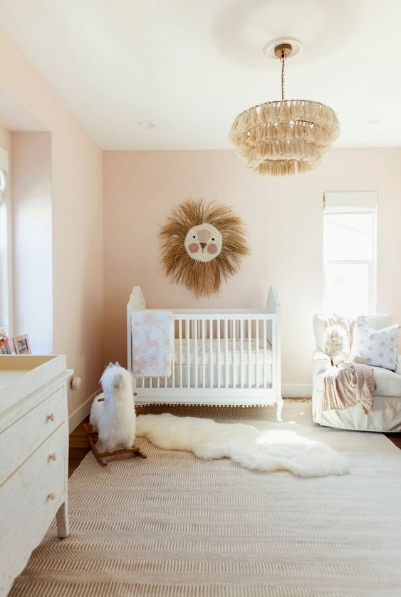 a neutral boho nursery with white furniture, a lion artwork, a tassel chandelier, layered rugs and printed textiles