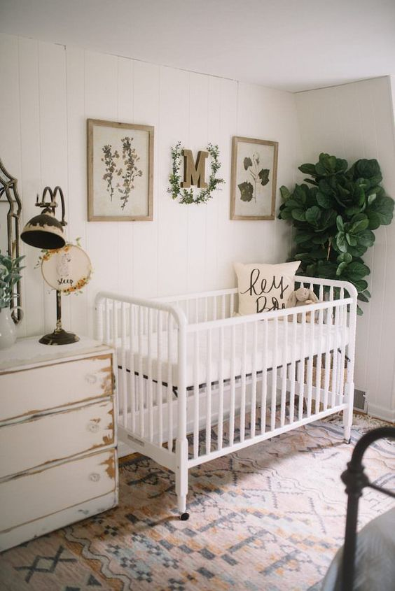 a neutral boho nursery with white shabby chic and modern furniture, layered rugs, a gallery wall and some plants is very cool