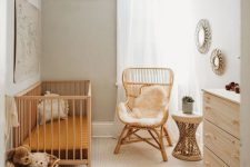 a neutral boho nursery with wicker furniture, a plywood dresser, mirrors and a basket with toys is a cozy idea