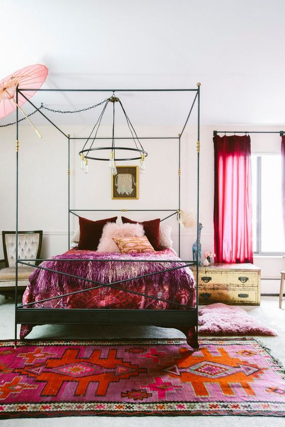 a neutral eclectic bedroom done with catchy gold and black furniture, bold red curtains, burgundy and red bedding and a colorful rug