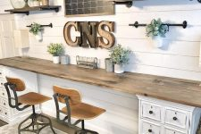 a neutral farmhouse home office with open shelves, a shared desk with white cabinets, a chalkboard and marquee letters on the wall