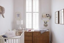 a neutral nursery with a double dresser, a white rocker and crib, a pendant lamp, a basket with toys and a gallery wall
