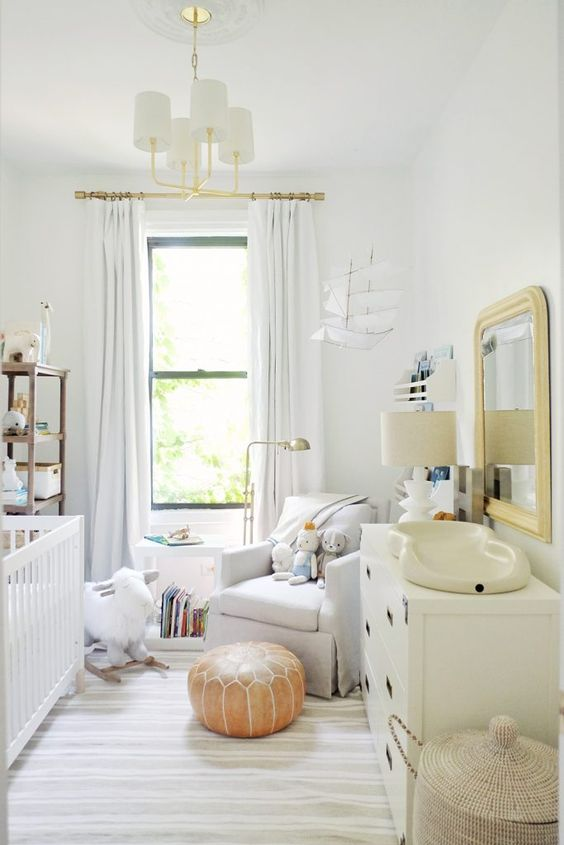 a neutral nursery with a striped rug, neutral textiles and upholstery, neutral furniture, lamps and mirrors plus storage units