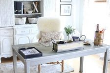 a neutral rustic home office with a large vintage white buffet, a light grey desk, a white chair, a metal sphere chandelier