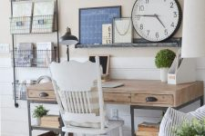 a neutral rustic home office with a wooden and metal desk, a metal box shelving unit, an open shelf with artworks and a round clock