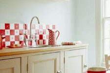 a neutral warm-toned kitchen with a red tile backsplash, linens and textiles and bold red tableware feels cozy and vintage