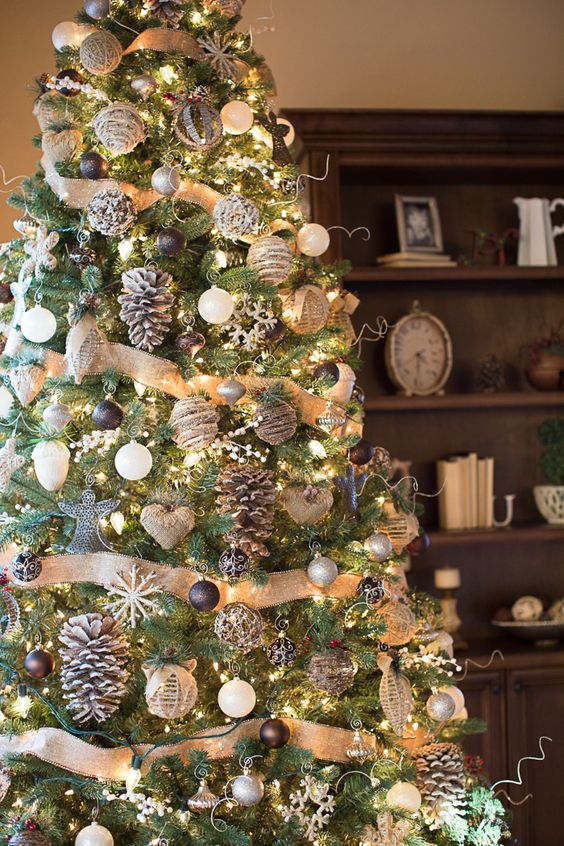 a pretty and chic rustic Christmas tree with burlap ribbons, black, grey and white ornaments, snowflakes, snowy pinecones and burlap hearts is amazing