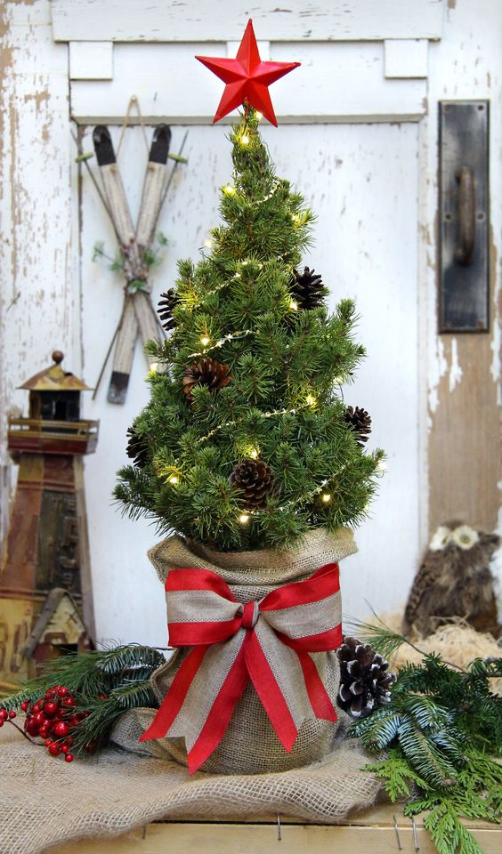 a pretty and simple tabletop Christmas tree decorated with lights, pinecones, with a star topper and a burlap sack with a bow