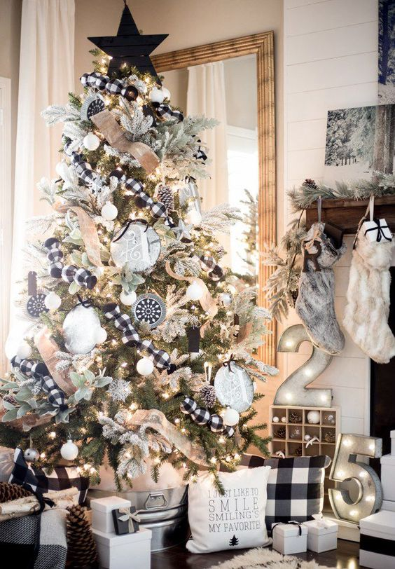 a pretty farmhouse Christmas tree with lights, plaid ribbons, white and black ornaments, bells and a black star on top
