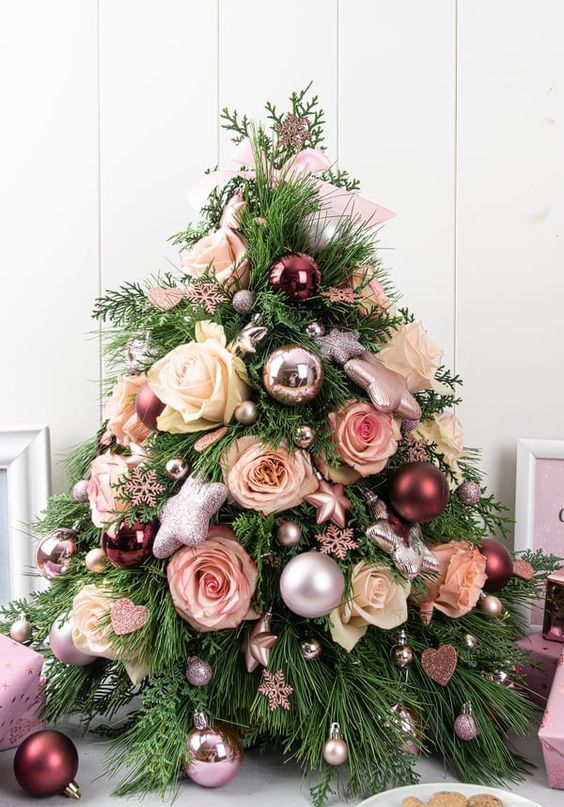 a pretty glam tabletop Christmas tree decorated with metallic and pastel ornaments, with glitter stars and pastel blooms