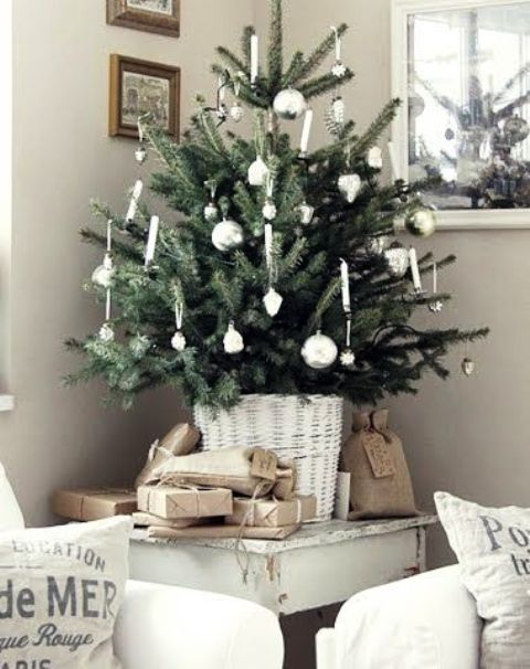 a pretty tabletop Christas tree with silver ornaments and candles put in a white basket is a beautiful and romantic thing