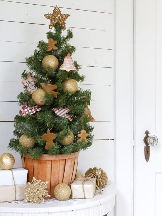 a pretty vintage tabletop Christmas tree decorated with gold glitter ornaments and with cookie cutter ones plus a twine stat on top