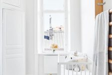 a pure white nursery with a white crib, a ladder for storage, a basket, some toys and pillows plus a pink rug for an accent