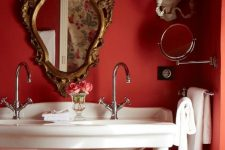 a refined and chic vintage red bathroom with a double sink vanity, a refined mirror, white towels and sconces