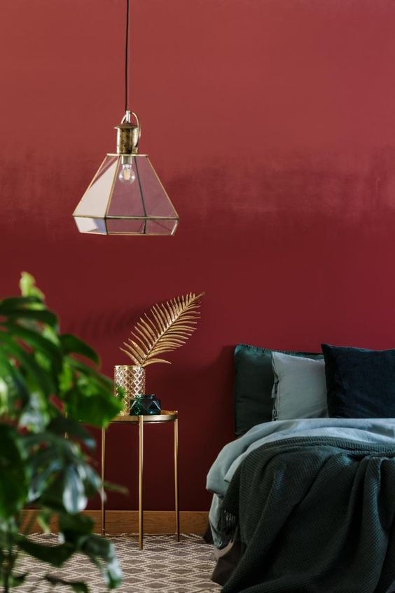 a refined and unique bedroom with a color block accent wall in red and burgundy, a bed with green and blue bedding, gold touches and a statement plant
