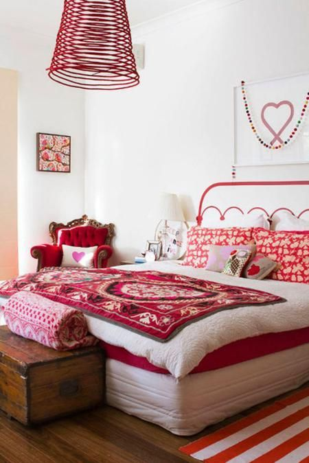 a refined bedroom with a mattress bed, a refined red chair, a pendant lamp and bright printed red bedding