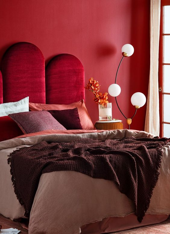 a refined bedroom with a red accent wall, a bold burgundy velvet upholstered headboard and a catchy floor lamp