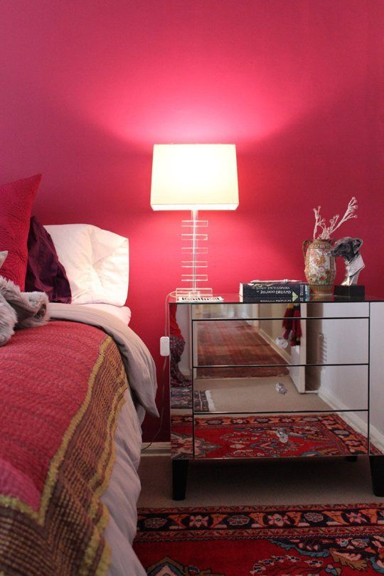 a refined mid century modern bedroom with a red accent wall, bold red and burgundy bedding, a printed rug and a mirror nightstand with a chic lamp