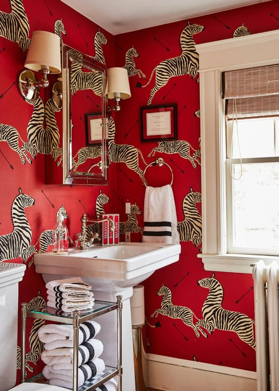 a refined red bathroom done with crazy red zebra print wallpaper, a large mirror cabinet, a glass shelf and vintage appliances