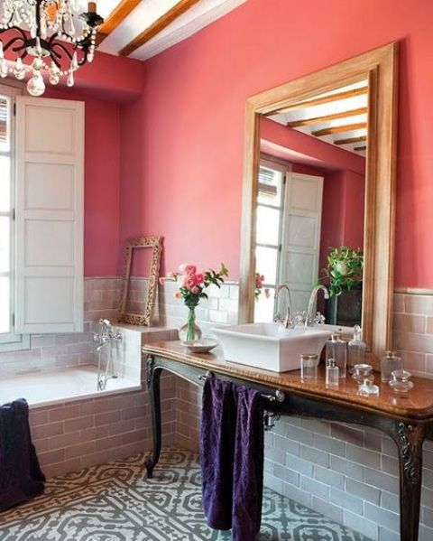 a refined red bathroom with grey tiles walls and a clad bathtub, a refined crystal chandelier and an exquisite vintage vanity table
