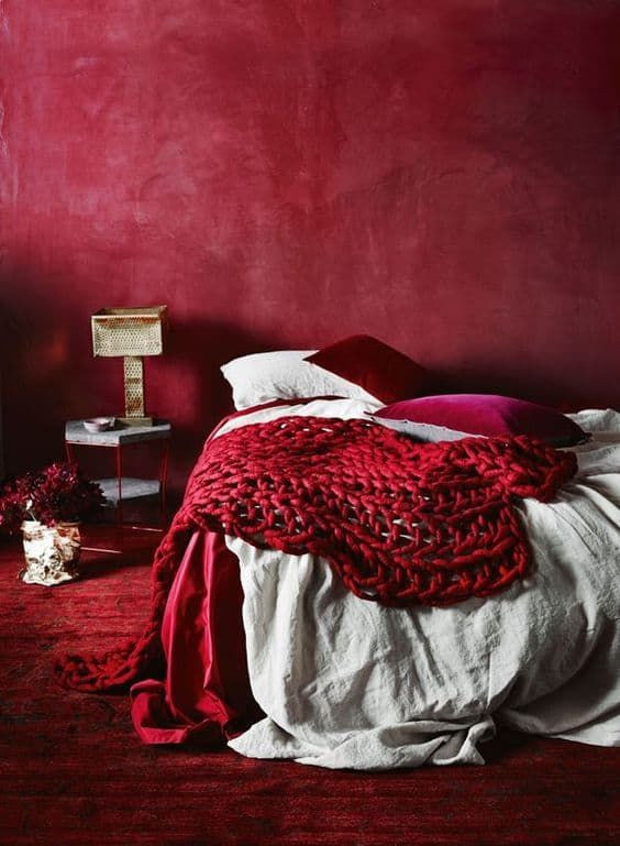 a refined red bedroom with a red plaster wall, a red rug, neutral, fuchsia and red bedding and a chic lamp