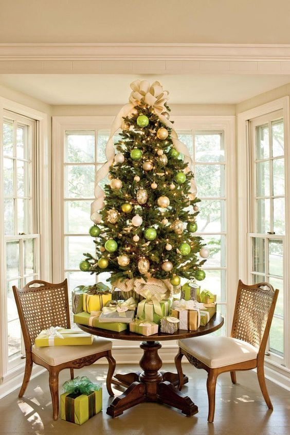 a refined tabletop Christmas tree decorated with green, gold and metallic ornaments and an oversized creamy bow on top