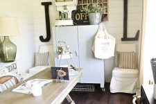 a relaxed neutral rustic home office with a white storage cabinet, a light-colored wooden desk, vintage lamps and greenery in buckets