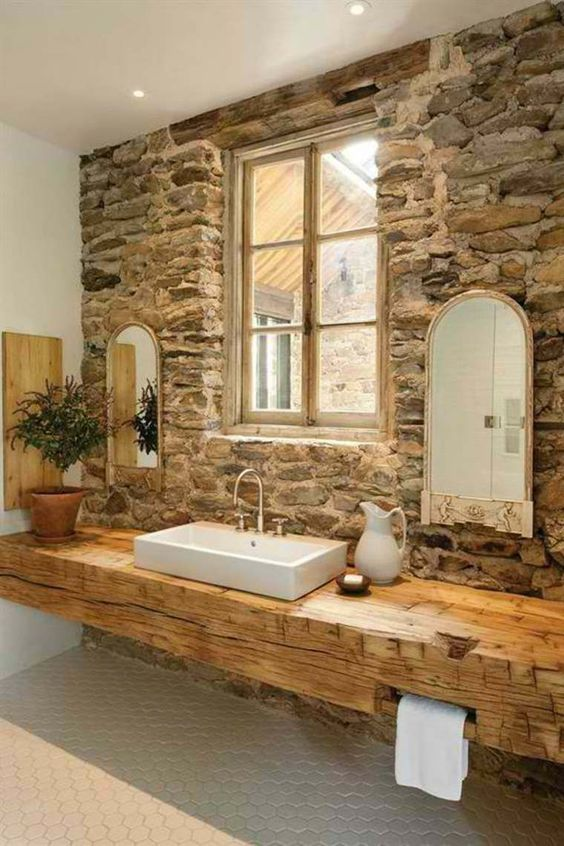 a rustic bathroom with a stone accent wall, a wood slab console table, arched mirrors and a plant in a pot