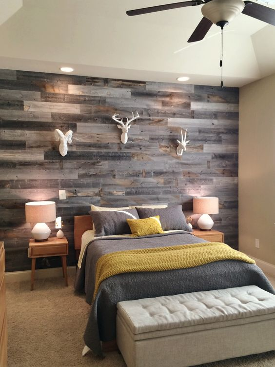 a rustic bedroom with a reclaimed wooden accent wall, simple furniture, faux taxidermy and grey and mustard bedding
