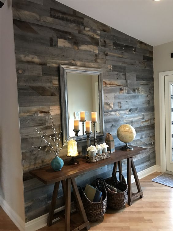 a rustic entryway with a reclaimed wooden wall, a trestle console, a mirror, baskets for storage and candles on the table