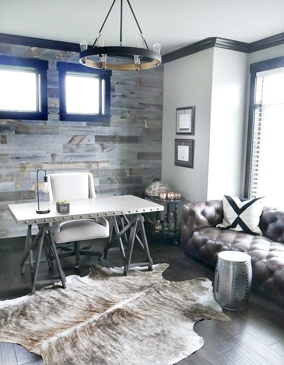 a rustic home office with a trestle desk, a white chair, a leather sofa, a metal stool, a metal chandelier and a faux fur rug