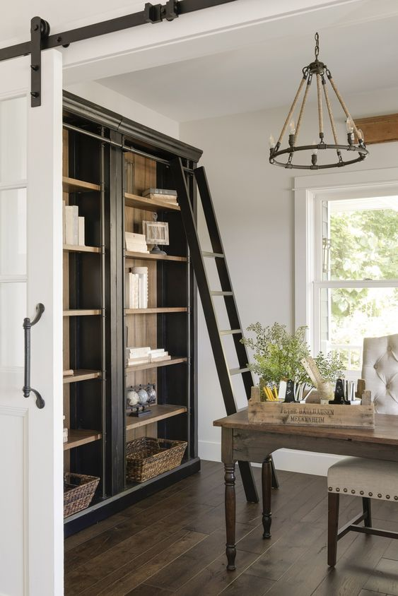 a rustic home office with a vintage wooden desk, a white chair, a metal chandelier, a large storage unit and a ladder