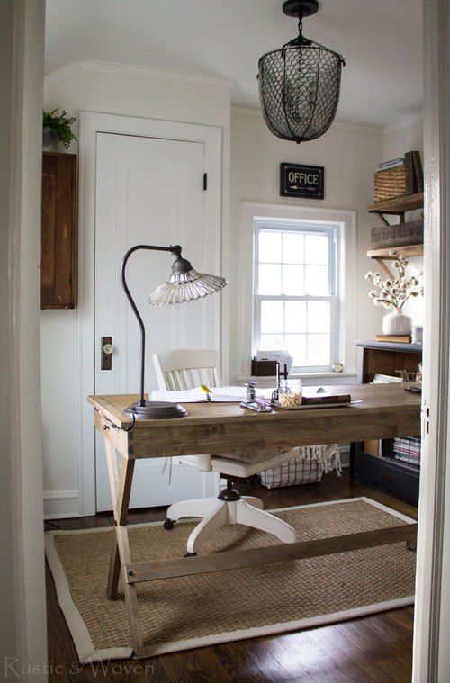 a rustic home office with a woven rug, a wooden trestle desk, wooden shelves and a wooden console table plus a mesh chandelier