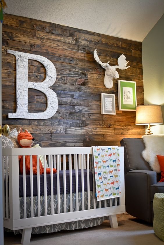 a rustic nursery with a dark stained wooden wall, neutral furniture, faux taxidermy and colorful bedding is a bright and welcoming space