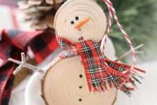 a rustic snowman ornament of wood slices, a plaid scarf and some sticks is ideal for Christmas
