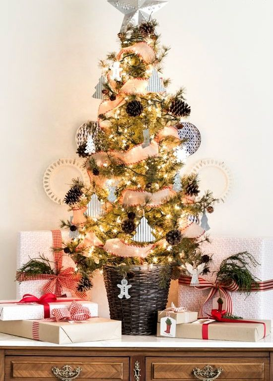 a rustic tabletop Christmas tree with lights, pinecones, little paper and clay ornaments and a basket as a base