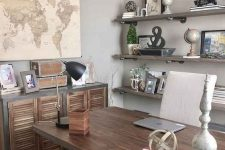 a rustic vintage home office with open industrial shelving, a wood and metal desk, a shutter sideboard and maps and artworks